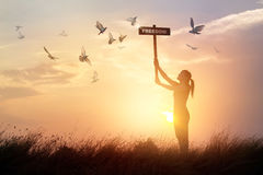 Woman holds a sign with word freedom and flying birds on sunset Royalty Free Stock Photo