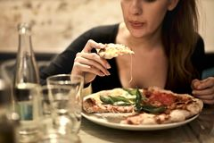 Woman Holds Sliced Pizza Seats by Table With Glass Stock Photo