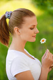 Woman holds small camomile Stock Photography