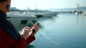 Woman holds smartphone on blurred background of port with yachts royalty free stock photo