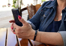 The woman holds the smartphone in hand Stock Images