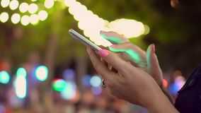 The woman holds the smartphone in hand on the street of the night city. Close-Up Woman Using Smart-Phone In The City stock video