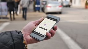 Woman holds smartphone with ride sharing app as driver arrives. A woman holds a smartphone with a ride sharing app displaying her driver has arrived. Fictional stock footage