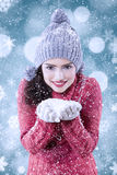 Woman holds snow with bokeh background Royalty Free Stock Image