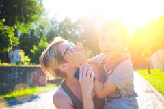 A woman holds son on hands. A women holds a son in her arms and hugs him, mom messing around with a child Stock Photo
