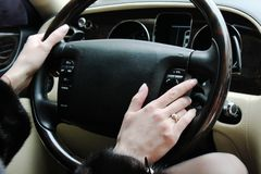 A woman holds the steering wheel of a luxury car. stock photos