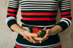 Woman holds strawberries in her hands Royalty Free Stock Photos