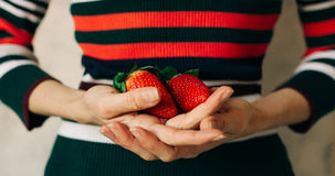Woman holds strawberries in her hands Stock Photo