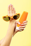 Woman holds sunglasses sunscreen lotion Stock Photography