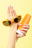 Woman holds sunglasses sunscreen lotion Stock Photo