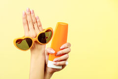 Woman holds sunglasses sunscreen lotion Royalty Free Stock Image