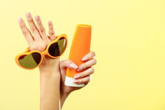 Woman holds sunglasses sunscreen lotion Royalty Free Stock Images