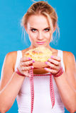 Woman holds sweet bun recommending non sugar diet. Unhealthy nutrition overweight concept. Fit female saying no to sweet dessert. Woman dietician holding sweet royalty free stock image