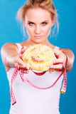 Woman holds sweet bun recommending non sugar diet. Unhealthy nutrition overweight concept. Fit female saying no to sweet dessert. Woman dietician holding sweet stock photography