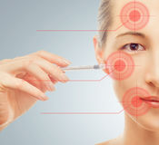 Woman holds a syringe near the face Stock Photo