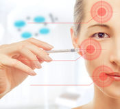 Woman holds a syringe near the face Royalty Free Stock Image