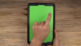 A woman holds a tablet PC with a green screen for your own custom content. stock footage