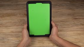 A woman holds a tablet PC with a green screen for your own custom content.