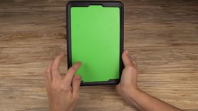 A woman holds a tablet PC with a green screen for your own custom content. stock video