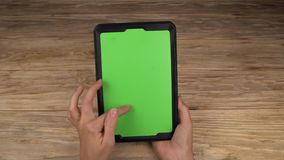 A woman holds a tablet PC with a green screen for your own custom content. stock video footage