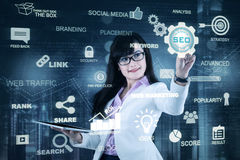 Woman holds tablet and pressing SEO icon. Young businesswoman holding a digital tablet and pressing SEO button on a virtual screen. SEO concept Stock Images
