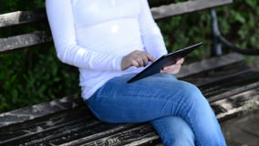 Woman holds and taps digital tablet computer on a wooden bench in the park. Stock Image