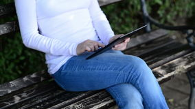 Woman holds and taps digital tablet computer on a wooden bench in the park. Stock Photography