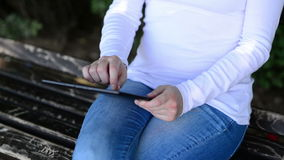 Woman holds and taps digital tablet computer on a wooden bench in the park. Royalty Free Stock Photo