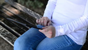Woman holds and taps digital tablet computer on a wooden bench in the park. Royalty Free Stock Photos