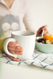 Woman holds tea cup and spoon with porridge and fruits Stock Photography