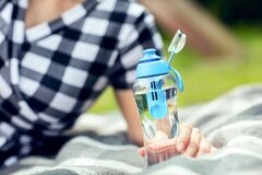 Free Woman Holds The Bottle Of Filtered Water Outdoors Stock Photo - 186859540