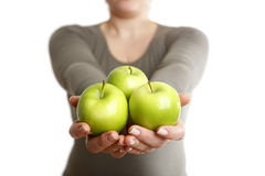 Woman holds three green apples into to camera Royalty Free Stock Image