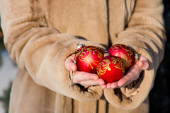 Woman  holds three red Christmas balls close-up Stock Images