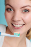 Woman holds toothbrush with toothpaste cleaning teeth Royalty Free Stock Image