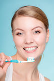 Woman holds toothbrush with toothpaste cleaning teeth Stock Photos