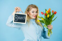 Woman holds tulips, board with text 8 march Royalty Free Stock Photography