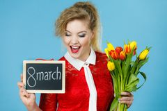 Woman holds tulips, board with text 8 march Royalty Free Stock Images