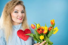 Woman holds tulips and red heart Stock Photo