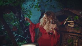 A woman holds two flasks in her hands. A witch in red dress stock footage
