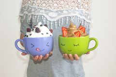 A woman holds two large mugs with painted faces, with whipped cream and berries. Chocolate mousse with strawberries and vanilla. Mousse with blackberries and stock image