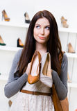 Woman holds two shoes in the shopping mall. And can't choose the one for her Royalty Free Stock Image