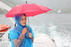 Woman holds umbrella at small boat Stock Photography