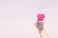 Woman holds up a red heart in hand stock photography