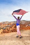 Woman holds US flag, Bryce Canyon National Park Royalty Free Stock Photo