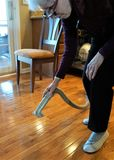 Woman holds vacuum over dirty floor. Wood floor has dirt and debris piled on it. Female with white hair holds silver nozzle of electric cleaning technology. Lady stock images