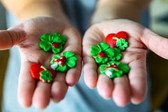 Woman holds various lucky charms in her hands, there are shamrocks, hearts and mushrooms stock photos