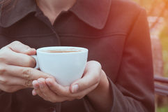 Woman holds white coffee cup Stock Photo