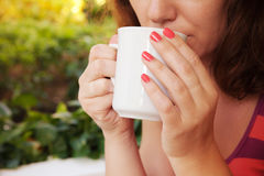Woman holds white cup of coffee in her hands Royalty Free Stock Photo