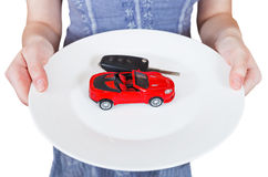 Woman holds white plate with new red car Royalty Free Stock Photos