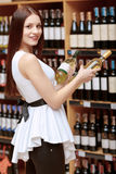 Woman holds a wine bottle in the store. Better take both. Portrait of an attractive young woman holding two wine bottles copyspace near the shelves of the store stock photography